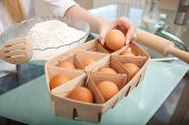 stock photo of human egg  - Close up of female hands taking an egg from basket on table - JPG