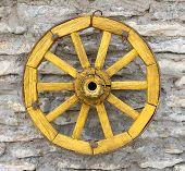 stock photo of wagon wheel  - Old Yellow Antique Wagon Wheel on Limestone Background - JPG