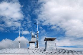 foto of antenna  - Light gray metal roof with two chimneys and different antennas against blue and white sky - JPG