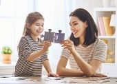 Happy family. Mother and daughter do puzzles together. Adult woman teaches child to solve puzzles. poster