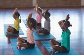 School kids meditating during yoga class in basketball court at school gym poster