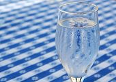 stock photo of chug  - A glass of iced water standing on a blue and white tablecloth ice cubes in glass and condensed water on glass due to heat - JPG
