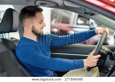 poster of Happy Young Visitor Of Auto Salon Sitting At Front Seat In New Car. Brunette Man With Beard Holding