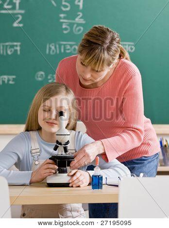 Постер, плакат: Учитель помогает отрегулировать микроскопа в классе науки школы студент, холст на подрамнике