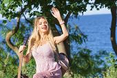 Hippie Looking Young Adult Woman Wearing Gypsy Outfit Having Acoustic Guitar. Female Playing Music I poster