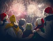 New Year holiday. Parents and daughters children girls are watching fireworks. Happy family on snowy poster