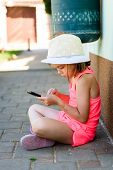 Girl Child Using Smartphone For Games Or Internet On Vacations. Little Girl Is Playing With Smartpho poster
