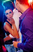 picture of cheating  - Attractive woman flirting with man in nightclub - JPG
