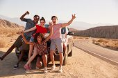 Young adult friends on road trip have fun posing by the car poster
