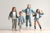 The Portrait Of Cute Little Kids Boy And Girls In Stylish Jeans Clothes Looking At Camera Against Wh poster
