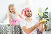 Cute Little Daughter In Tutu Skirt And Smiling Father In Pink Wig Looking At Mirror poster