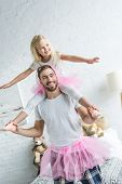 Happy Father In Pink Tutu Skirt Carrying Adorable Little Daughter On Neck poster