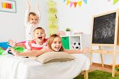 childhood, leisure and family concept - happy little kids having fun in bed at home poster