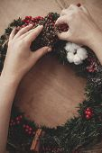 Hands Making Rustic Christmas Wreath, Holding Herbs At Fir Branches, Red Berries , Pine Cones, Cotto poster