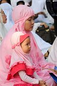 JAKARTA, INDONESIA - SEPTEMBER 20: Mother and daughter perform prayers outside a mosque on Hari Raya