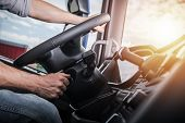 Euro Truck Driving. Modern Semi Truck Cabin Interior. Caucasian Trucker Placing Hand On A Steering W poster