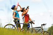 Attractive, healthy couple drink from their water bottles on mountain bikes. active outdoor lifestyl