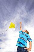 Постер, плакат: Молодой мальчик летит желтая змея в ветреную летний день