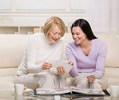 stock photo of mother daughter  - Adult mother and daughter enjoying photo album in livingroom - JPG