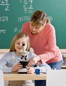 Постер, плакат: Учитель помогает отрегулировать микроскопа в классе науки школы студент