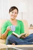 stock photo of reading book  - Woman relaxing on sofa in livingroom enjoying reading a book and drinking coffee - JPG