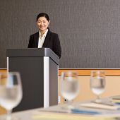 stock photo of asian woman  - Businesswoman standing behind podium preparing to give presentation in conference room - JPG