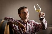 Smiling winemaker looking at glass of white wine for quality testing, leaning on barrel in wine cell