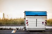 pic of dumpster  - a white and weathered dumpster at the street side - JPG
