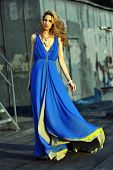 Fashion model posing sexy wearing long blue evening dress on rooftop location