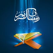 foto of islamic religious holy book  - Arabic Islamic calligraphy of text of Ramadan Kareem with Islamic religious holy book Quran Shareef on shiny abstract blue background - JPG