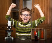 Happy boy with a microscope and colorful flasks