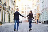 stock photo of heterosexual couple  - Happy young couple in love walking at city - JPG