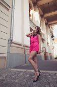 stock photo of jumpsuits  - Fashion glamorous and attractive woman dressed in a sexy sleeveless pink jumpsuit posing in full body length with long legs - JPG