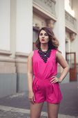 picture of jumpsuits  - Fashion glamorous and attractive woman dressed in a sexy sleeveless pink jumpsuit with a hand in her hair - JPG