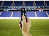 picture of realism  - Hand holding television remote for watching sports in 3D - JPG