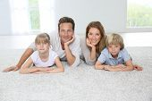 stock photo of four  - Happy family of four laying on carpet at home - JPG