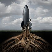 stock photo of glory  - Rooted down concept with an aging rocket ship being held down by growing tree roots as a metaphor for uncompetitive and abandoned strategy of past forgotten potential and broken dreams of glory - JPG