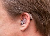 Постер, плакат: Close up of a human ear with hearing aids