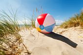 image of dune  - Beach ball resting in sand dune concept for childhood summer vacations - JPG