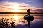 stock photo of jerks  - Mature man fishing from the boat on the pond at sunset - JPG