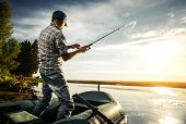 picture of jerks  - Mature man fishing from the boat on the pond at sunset - JPG