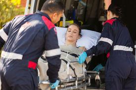 picture of ambulance  - paramedics taking unconscious patient into an ambulance - JPG