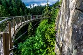 stock photo of cliffs  - Beautiful Capilano Cliff Walk Suspension Bridge with Tourists Enjoying the View - JPG