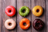 picture of donut  - Delicious donuts with glaze on wooden background - JPG