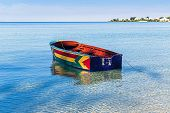 stock photo of jamaican  - A colorful Jamaican boat floating along the shores of Bloody Bay - JPG