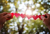picture of sweethearts  -  hands holding a string of paper hearts up to the sun during sun - JPG