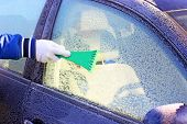 foto of ice-scraper  - scraping the windshield of a car at winter - JPG