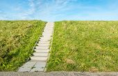 stock photo of dike  - A concrete staircase between the grass of a dike on a sunny day in autumn - JPG