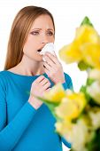 stock photo of sneezing  - Young woman holding handkerchief near face and sneezing while standing isolated on white - JPG