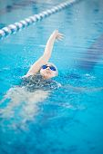 image of crawling  - Young woman in goggles and cap swimming back crawl stroke style in the blue water indoor race pool - JPG